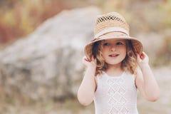 Lycklig liten flicka som utomhus bär en hatt Arkivfoto