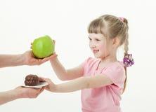 Lycklig liten flicka som väljer ett grönt äpple och vägrar en kaka royaltyfri fotografi