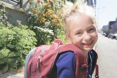 Lycklig liten flicka utanför med ryggsäcken Arkivbilder