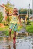 Lycklig liten flickabanhoppning i gummistöveler i en pöl i en sommardag arkivbilder