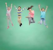 Lycklig liten flickabanhoppning i luft över skolförvaltning Arkivfoton