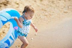 Lycklig liten flickabarnbadning med uppblåsbar cirkel- och hagyckel i havet fotografering för bildbyråer