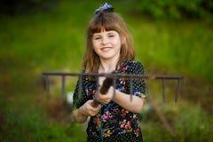 Lycklig liten flickahjälp uppfostrar i trädgård med krattar arkivbilder