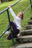 Lycklig liten flickaklättringräcke Arkivbild