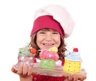 Lycklig liten flickakock med muffin Royaltyfri Bild