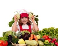 Lycklig liten flickakock med sunda grönsaker royaltyfri foto
