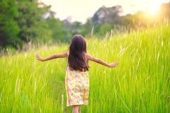 Lycklig liten flickaspring på äng Royaltyfria Foton
