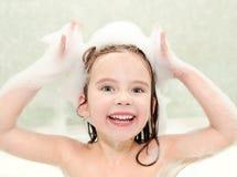 Lycklig liten flickatvagning i bad med skum Royaltyfria Foton