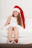 Lycklig liten flickaunge i den santa hatten Jul Fotografering för Bildbyråer
