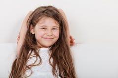 Lycklig liten flickaunge som kopplar av på soffan Royaltyfri Bild