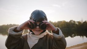 Lycklig liten flygarepojke som bär retro pilot- exponeringsglas som kör längs solnedgångsjön som låtsar för att vara en plan ultr stock video