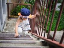 Lycklig liten gullig flicka som klättrar trappan till det upstair Lyckligt arkivbild