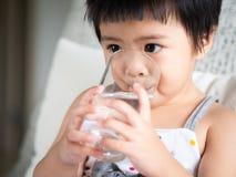 Lycklig liten gullig flicka som rymmer ett exponeringsglas och dricker vattnet C arkivbilder