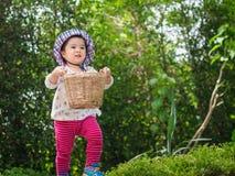 Lycklig liten gullig flicka som rymmer korgen och springen i garden arkivfoto
