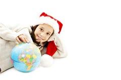 Lycklig liten jultomten med ett jordklot Arkivbild
