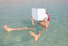 Lycklig liten jultomten som läser tidskriften på det döda havet Royaltyfri Bild