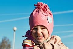 Lycklig liten le flicka med en blå himmel bakom Arkivfoton