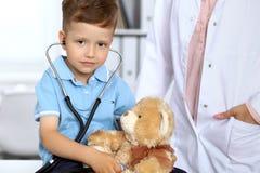 Lycklig liten patient efter vård- examen Liten doktor som undersöker en leksakbjörn med stethoscop royaltyfri bild