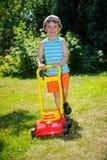 Lycklig liten pojkehjälp med att arbeta i trädgården med hans gräsklippare Royaltyfria Foton