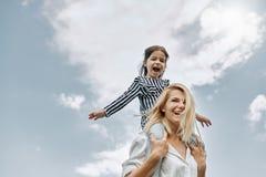 Lycklig liten rolig dotter på en ridtur på axlarnaritt med hennes lyckliga moder på himmelbakgrunden Älska kvinnan och hennes lit arkivbilder
