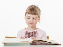 Lycklig liten skolaflicka som lär att läsa royaltyfria foton