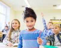 Lycklig liten skolaflicka över klassrumbakgrund Fotografering för Bildbyråer