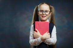 Lycklig liten skolflicka i enhetlig hållbok tätt royaltyfri fotografi