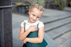 Lycklig liten skolflicka med boken som tillbaka går till utomhus- skola royaltyfri foto