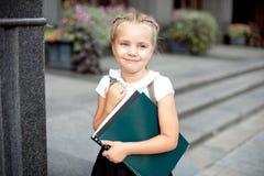 Lycklig liten skolflicka med boken som tillbaka g?r till utomhus- skola arkivbilder