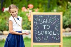 Lycklig liten skolflicka med en utomhus- svart tavla arkivfoton
