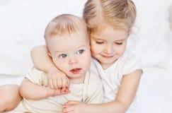 Lycklig liten syster som kramar hennes broder Arkivfoton
