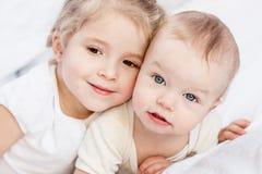 Lycklig liten syster som kramar hennes broder Royaltyfri Bild