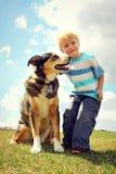 Lycklig liten unge utanför med hans hund Royaltyfri Fotografi