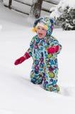 Lycklig litet barnflicka i varmt lag och stucken hatt som utanför kastar upp snö och har en gyckel i vintern, utomhus- stående royaltyfri fotografi