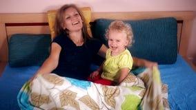 Lycklig litet barnflicka och moder som spelar i säng stock video