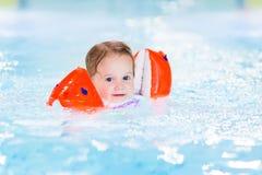 Lycklig litet barnflicka som har gyckel i en simbassäng Royaltyfria Bilder