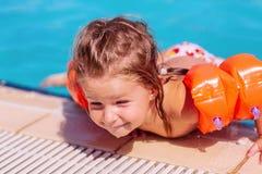 Lycklig litet barnflicka som har gyckel i en simbass?ng arkivfoto