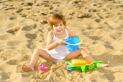 Lycklig litet barnflicka som leker med henne toys på stranden Arkivbilder