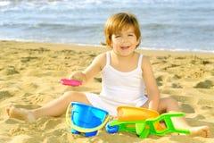 Lycklig litet barnflicka som leker med henne toys på stranden Royaltyfri Bild