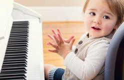 Lycklig litet barnflicka som spelar pianot Arkivfoton