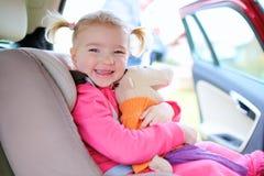 Lycklig litet barnflicka som tycker om säker tur i bilen Royaltyfri Foto