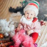 Lycklig litet barnpojke med en jultomtenhatt som ser kameran Royaltyfri Foto