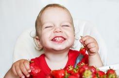 Lycklig litet barnpojke som äter jordgubbar Royaltyfri Fotografi