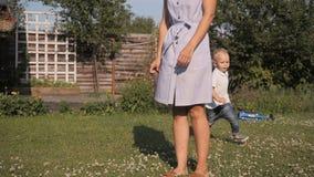 Lycklig Little Boy spring runt om hans mamma i trädgården lager videofilmer