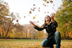 Lycklig livstid - kvinna som kastar leaves i fall Fotografering för Bildbyråer
