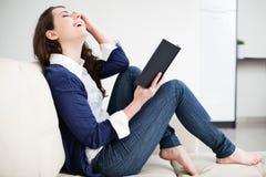 Lycklig läsebok för ung kvinna hemma Arkivbild