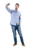 Lycklig lyckad affärsman som tar selfie som ser den smarta telefonen arkivfoto