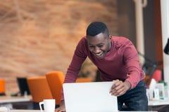 Lycklig lyckad afrikansk amerikanaffärsman i ett modernt startup kontor inomhus royaltyfri foto