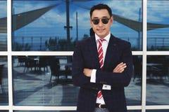 Lycklig lyckad manentreprenör i formella kläder som poserar mot kontorsbyggnad Royaltyfri Fotografi