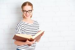 Lycklig lyckad studentflicka med boken arkivbild